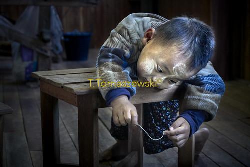 Chłopiec bawiący się sznurkiem z lotosu.Birma A boy playing with a string of lotus. Burma